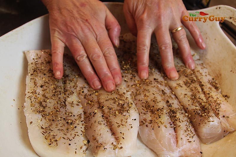 Patting ground spices into fish