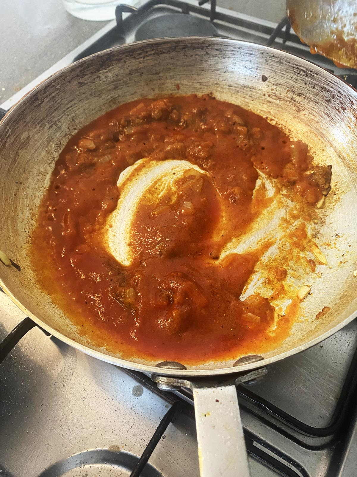 Adding tomato puree to pan