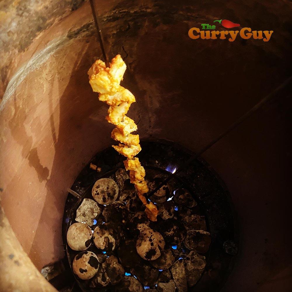 tandoori octopus cooking in tandoor oven