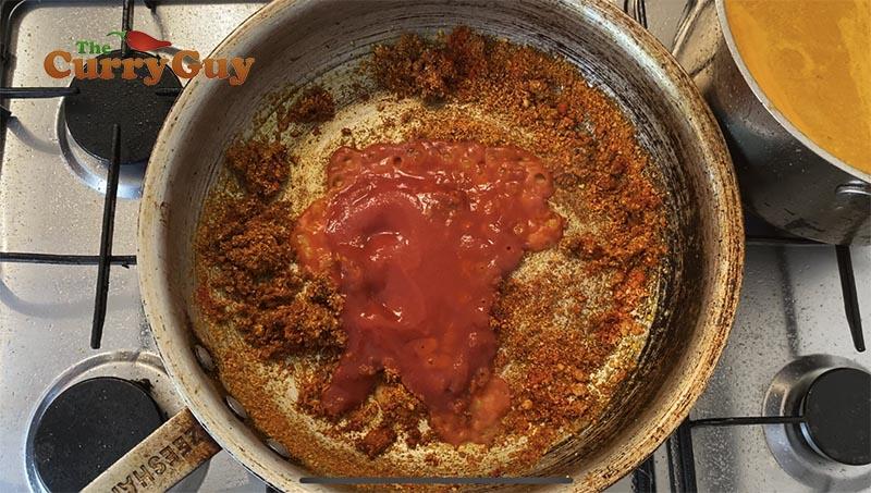 adding tomato puree to sauce
