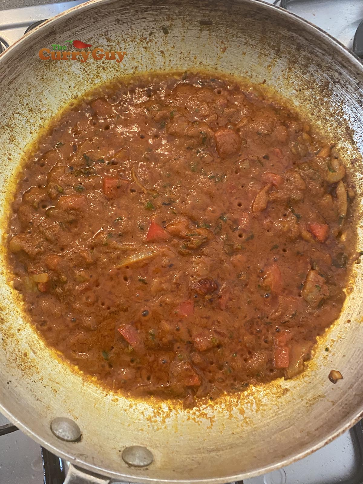Adding tomato puree to pan