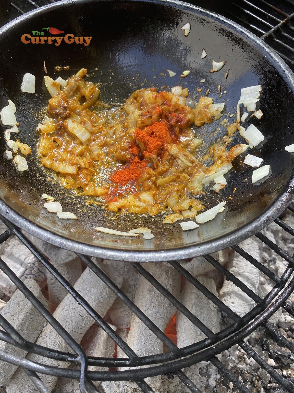 Adding ground spices to balti bowl
