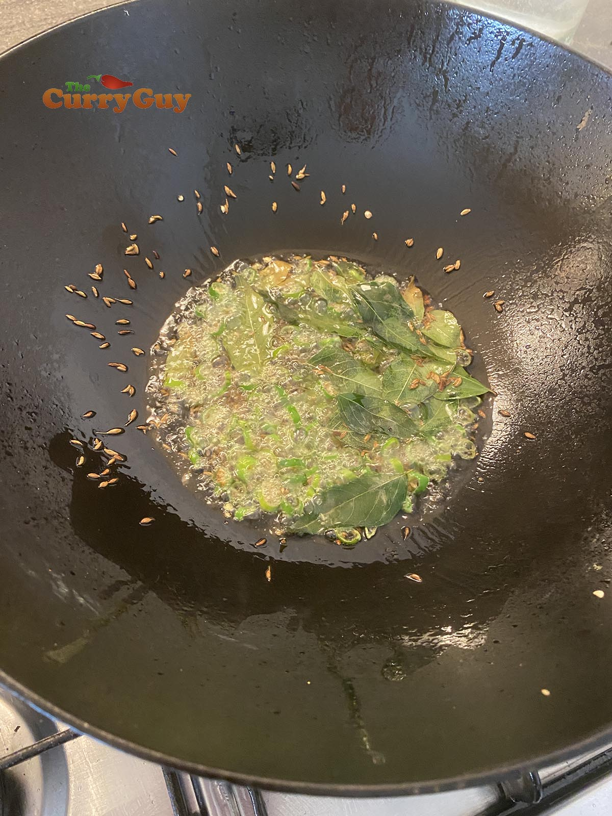 Adding curry leaves and cumin seeds to pan.