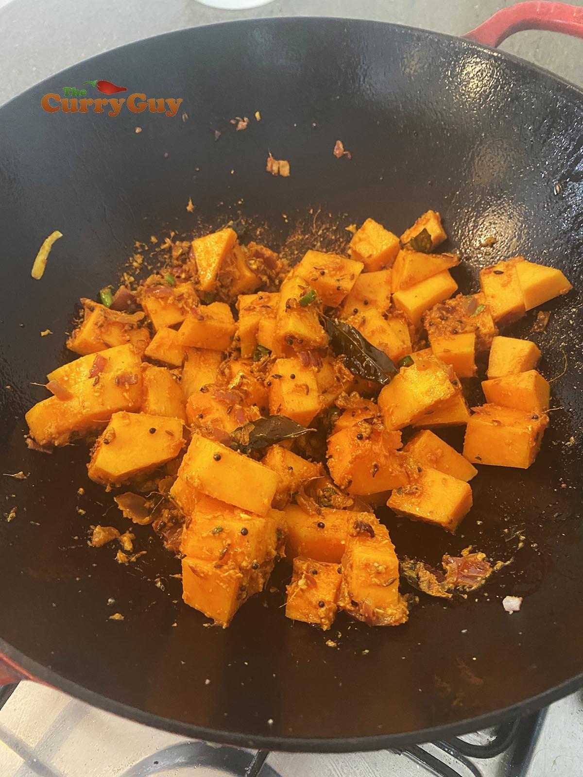 Adding butternut squash to the butternut squash curry