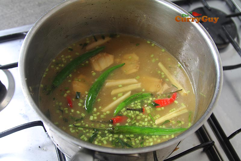 Adding vegetables to Thai soup