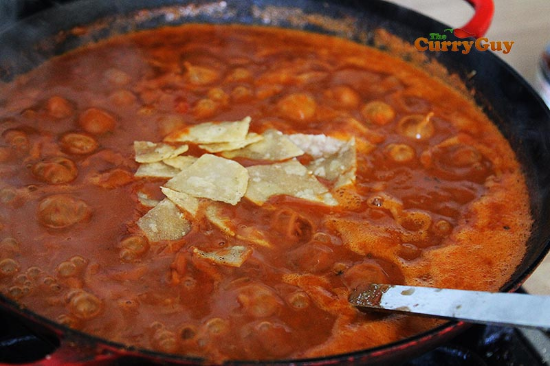 Adding handful of corn chips to sauce