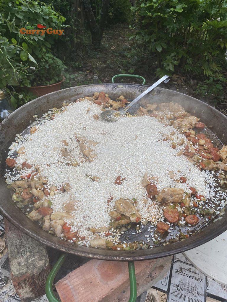Adding rice to paella