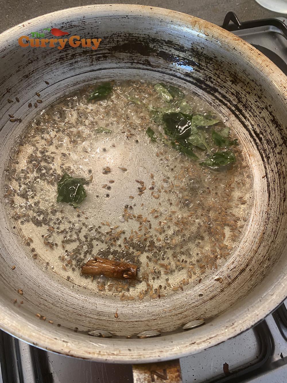 adding cinnamon, cumin, fenugreek and curry leaves