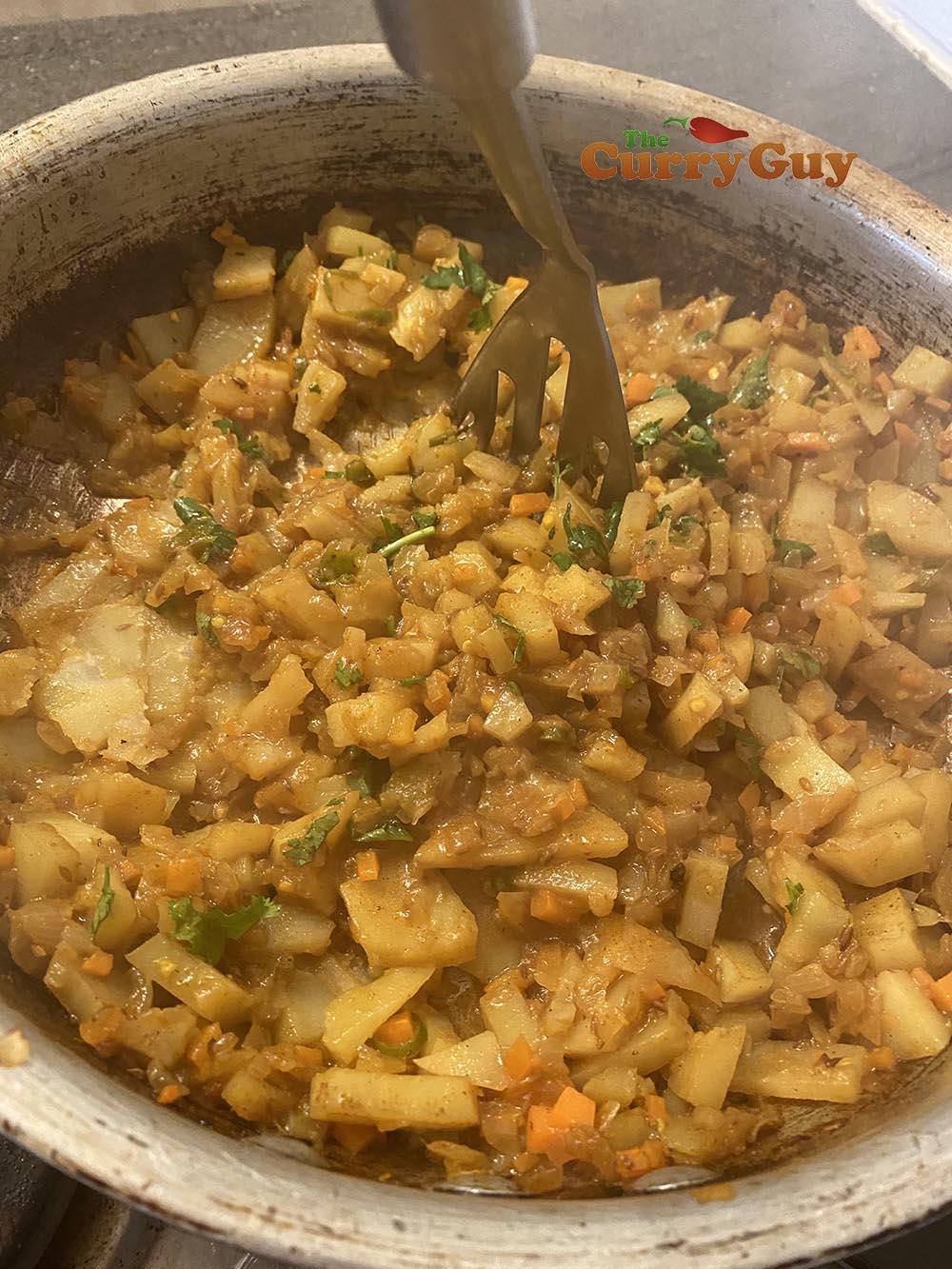 Using potato masher to crush potatoes