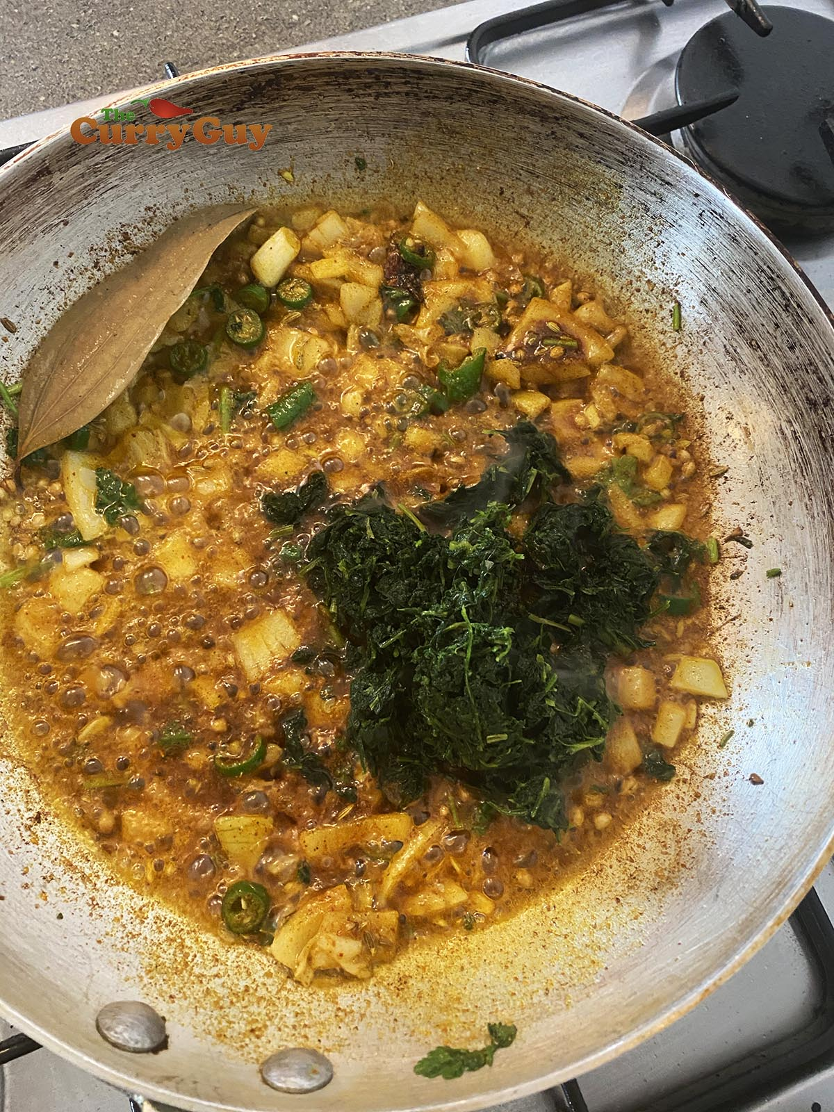 Adding methi to curry.