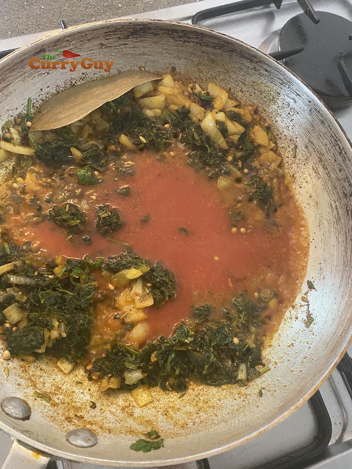 Adding tomato puree to pan.