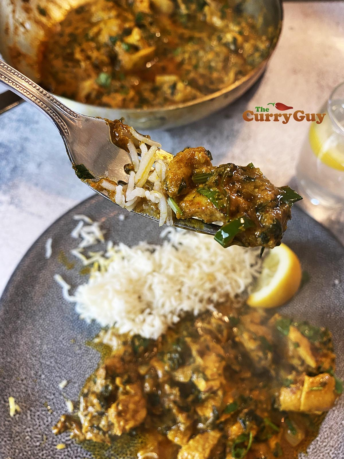 Chicken methi curry on a fork.