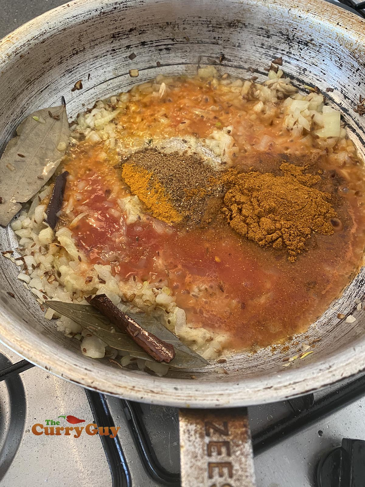 adding tomato puree and ground spices to the pan