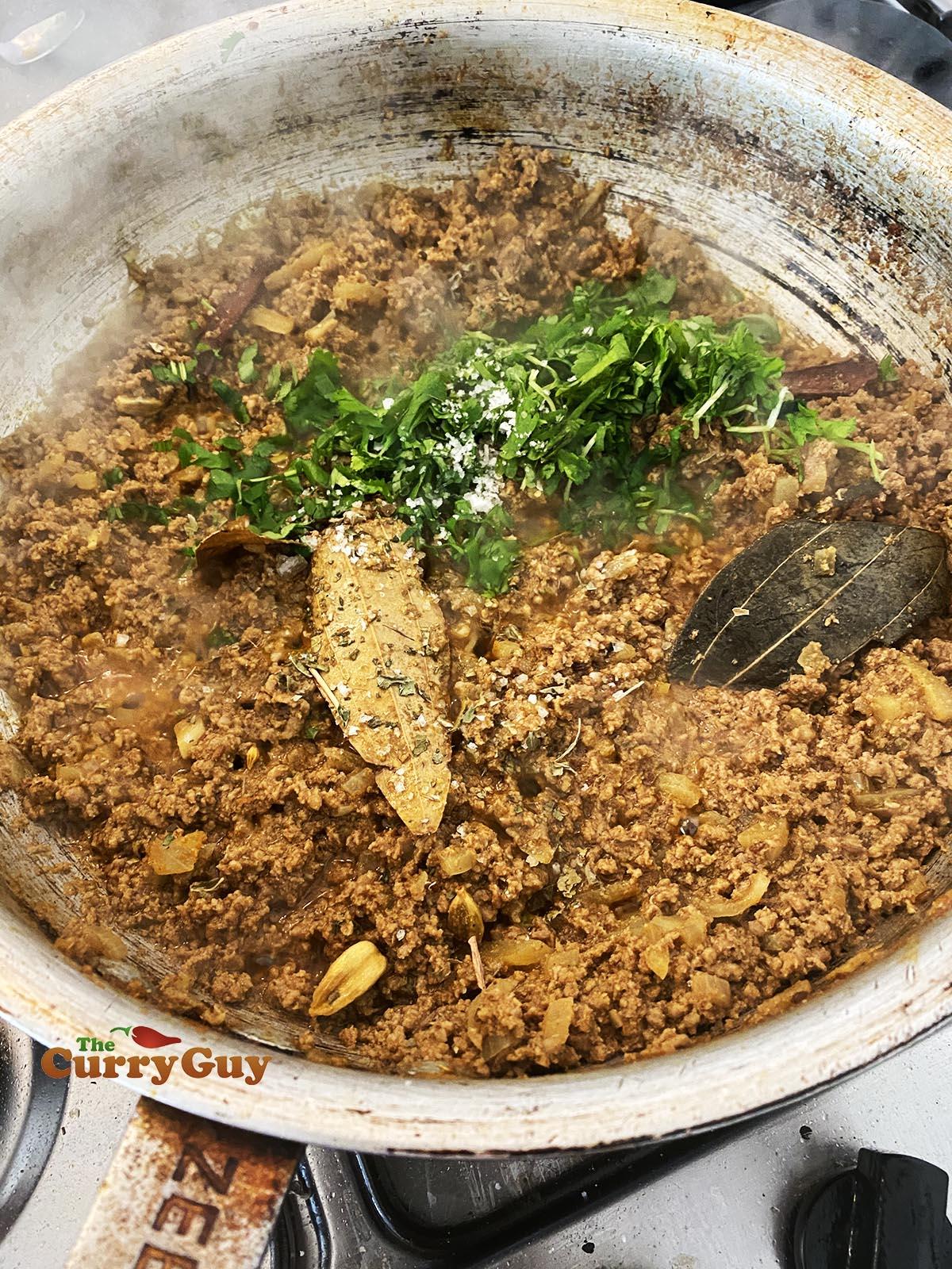 Adding coriander (cilantro) and kasoori methi to the pan.