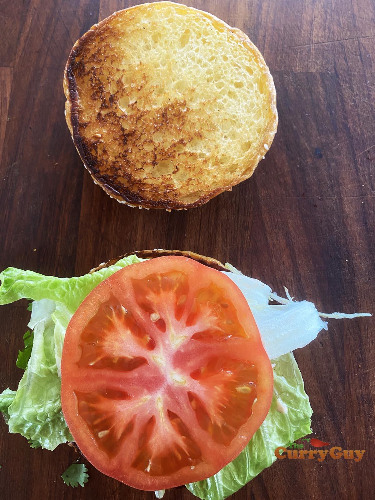Adding tomato to burger