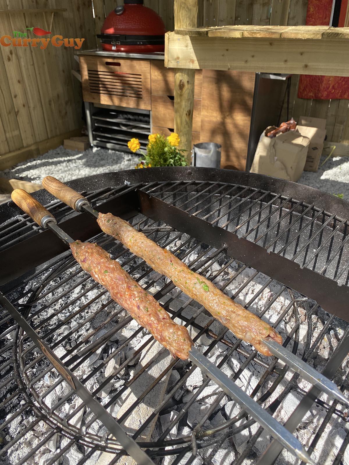Kebabs cooking over coals.